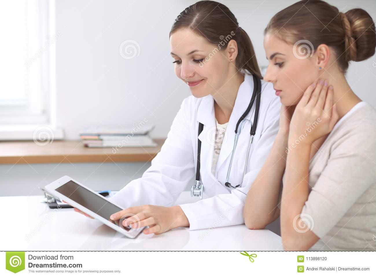 Doctor and patient sitting at the desk. The physician or therapist makes a diagnosis. Health care, medicine and patie