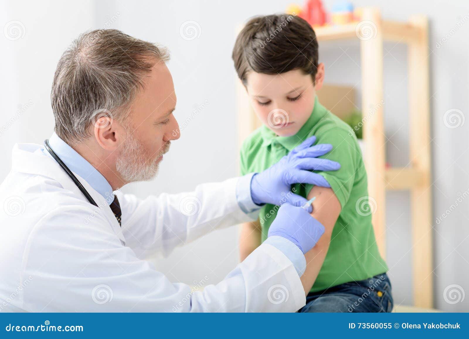 Doctor pediatrician injecting vaccine