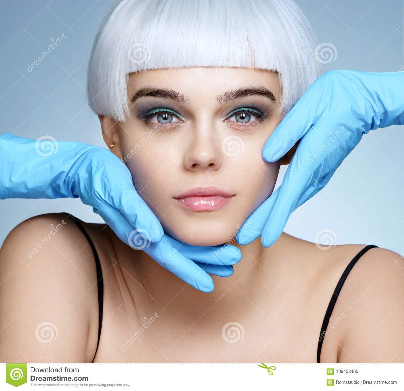Doctor`s hands in gloves touching face of beautiful woman