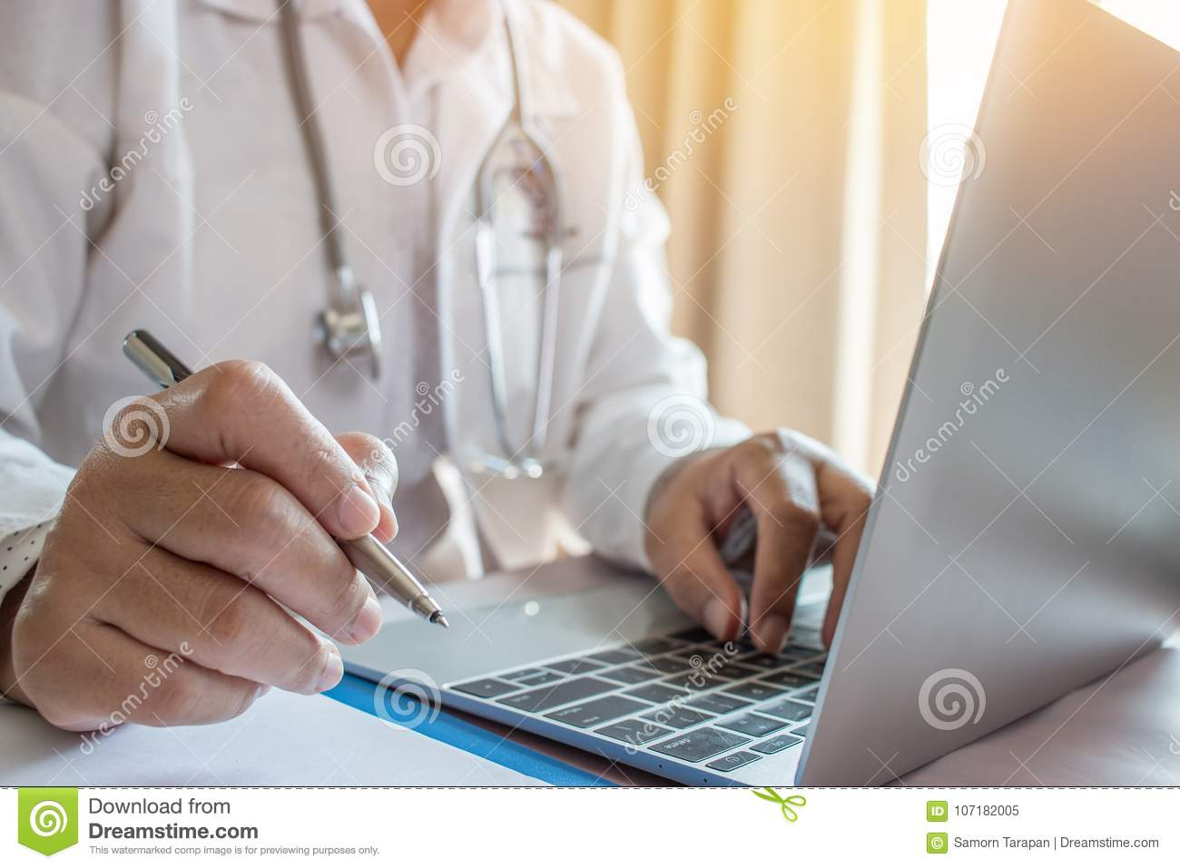 doctor s writing and working on laptop computer writing prescri