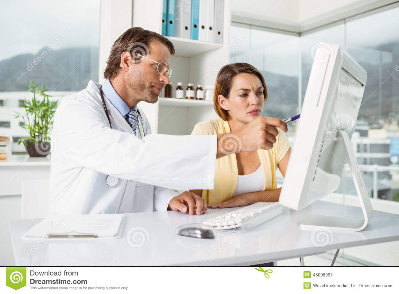 Young Female Medical Doctor Updating Patient Computer Records With ...