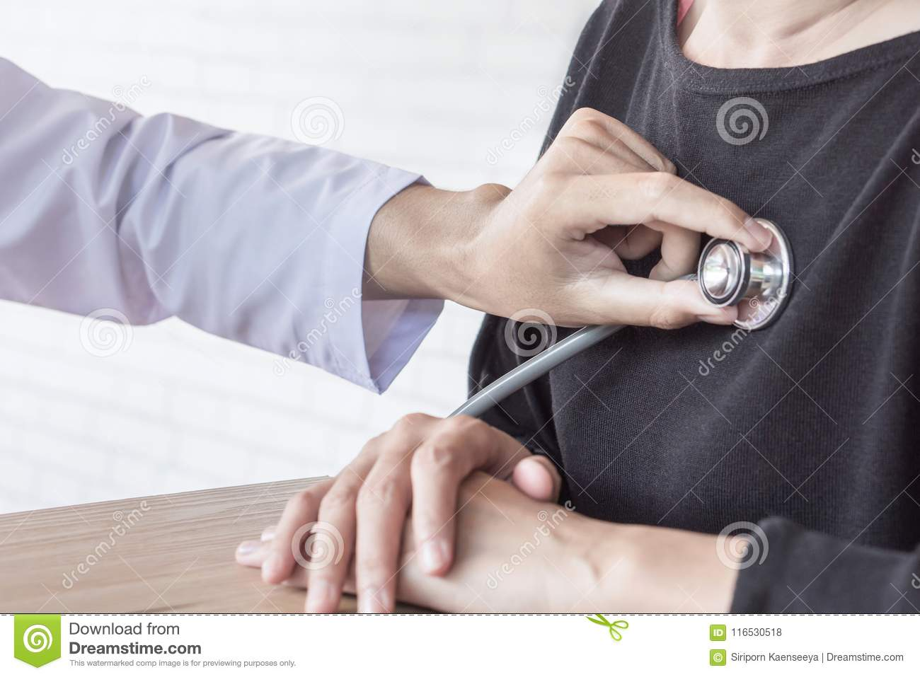 Doctor with stethoscope in hand examining female patient heart beat