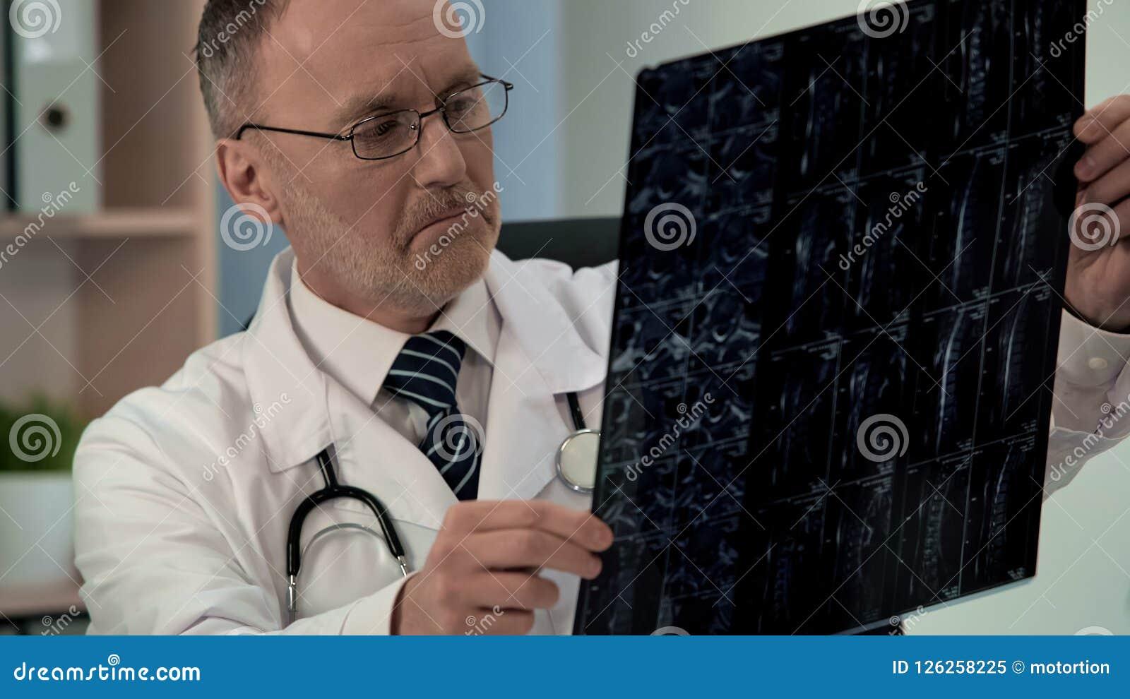 Doctor studying ill patients mri, finds damage in cervical vertebra, diagnostics