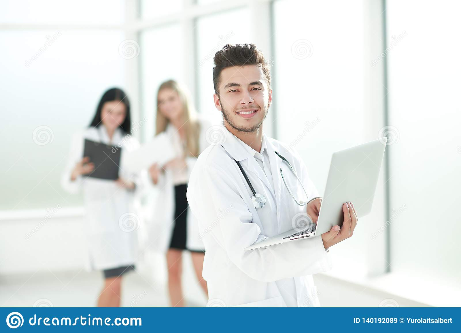 Doctor therapist uses a laptop while standing in the hallway of the clinic