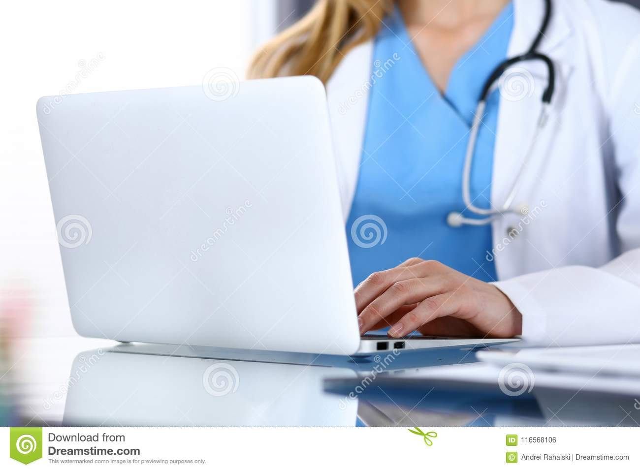 Doctor typing on laptop computer while sitting at the glass desk in hospital office. Physician at work. Medicine and
