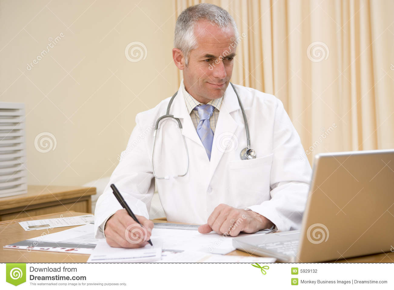 Doctor using laptop and writing in doctor s office