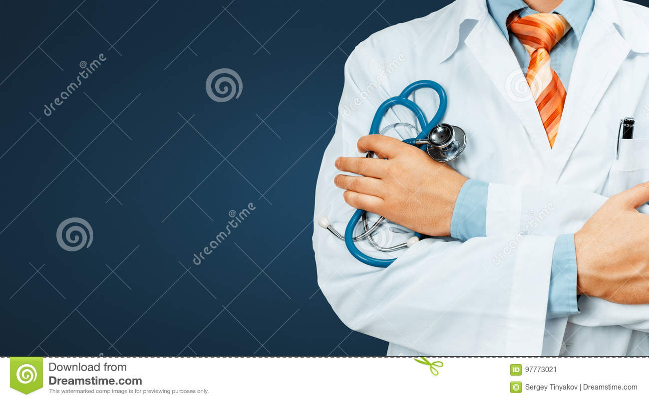 Doctor In White Coat With A Stethoscope Crosses His Arms Over His Chest Copy-space On Blue Background. Healthcare Medicine Concept