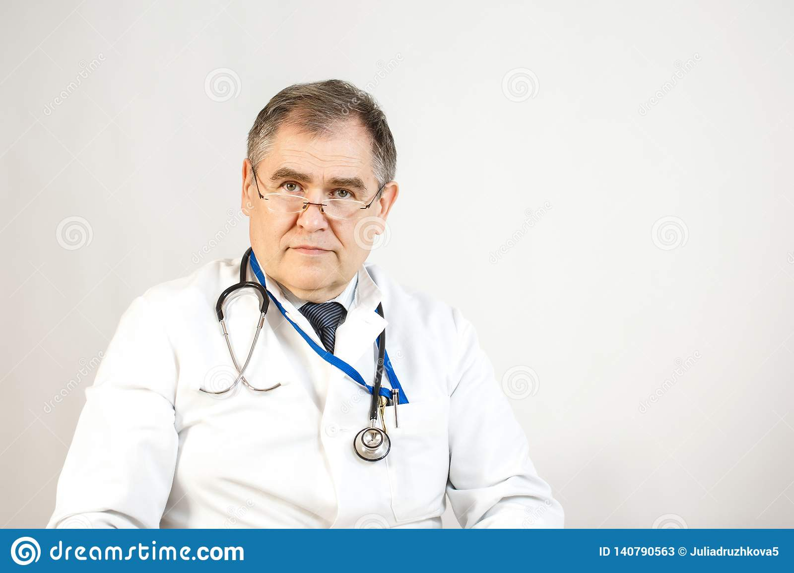 A doctor in a white coat and tie is looking forward, a whist has a stethoscope and a badge on his neck, and there are pens in his