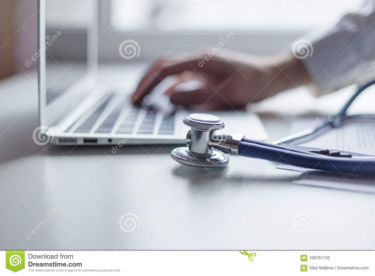 Doctor working with laptop computer in medical workspace office. Focus on stethoscope