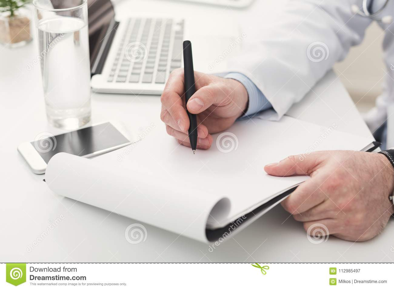 Doctor writing notes at office, closeup