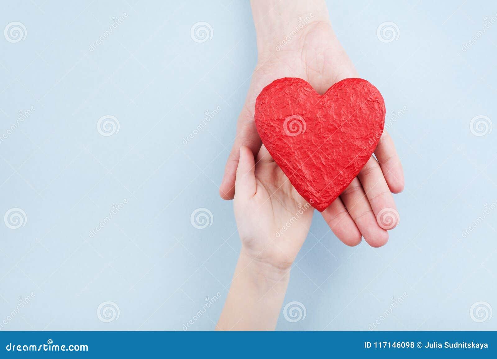 Doctor y niño que llevan a cabo el corazón rojo en manos Relaciones de familia, atención sanitaria, concepto pediátrico de la car