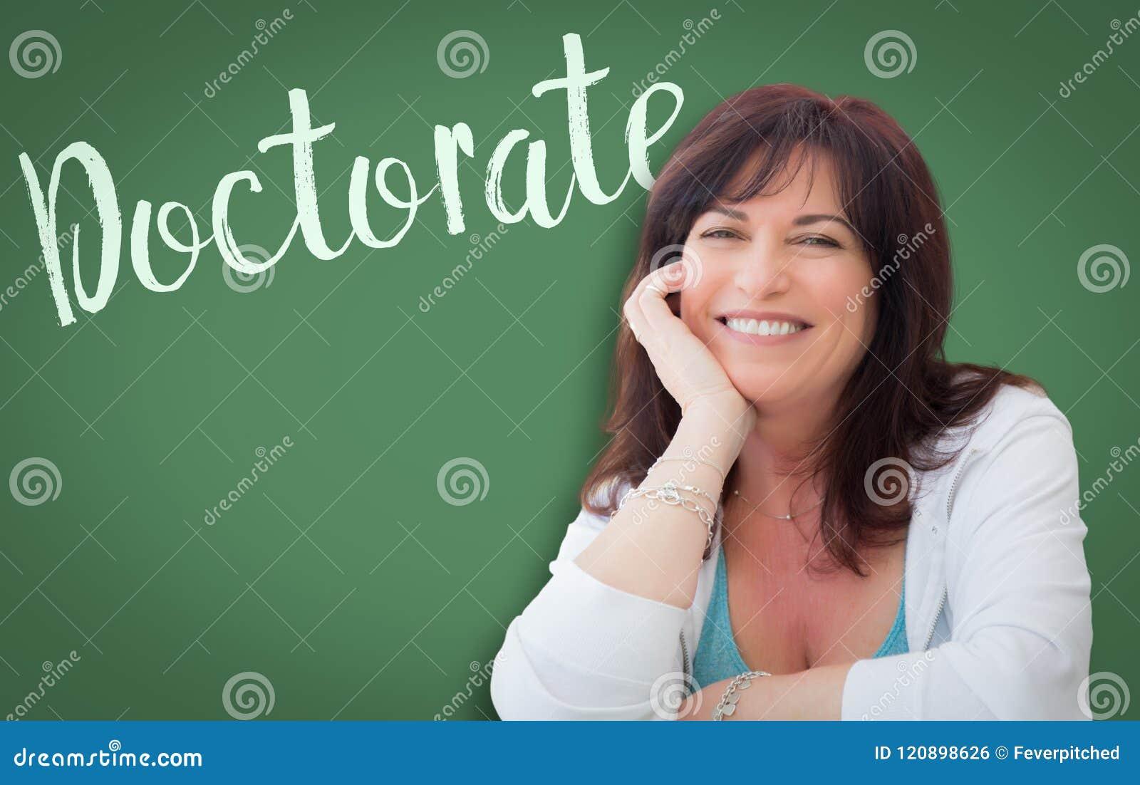 Doctorate Written On Green Chalkboard Behind Smiling Woman