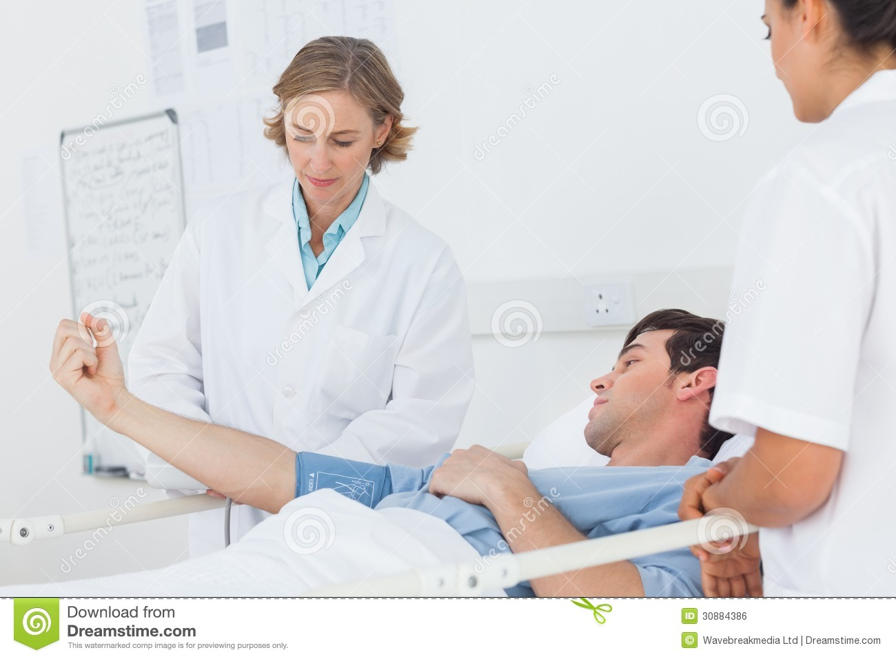 Doctors measuring the blood pressure of a male patient