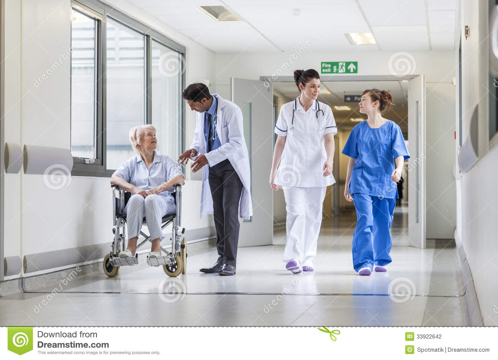 Doctors u0026 nurse in hospital corridor with senior female patient in ...