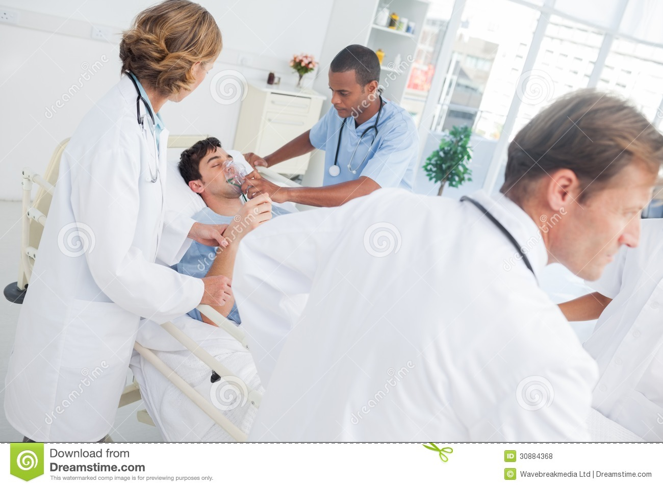 Sick Patient Pic : Doctors taking care of a sick patient lying in his sickbed.