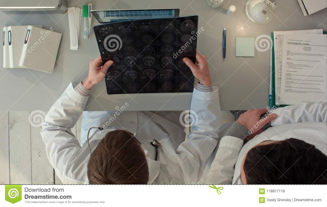 Doctors team having a discussion and review a magnetic resonance imaging. Top view