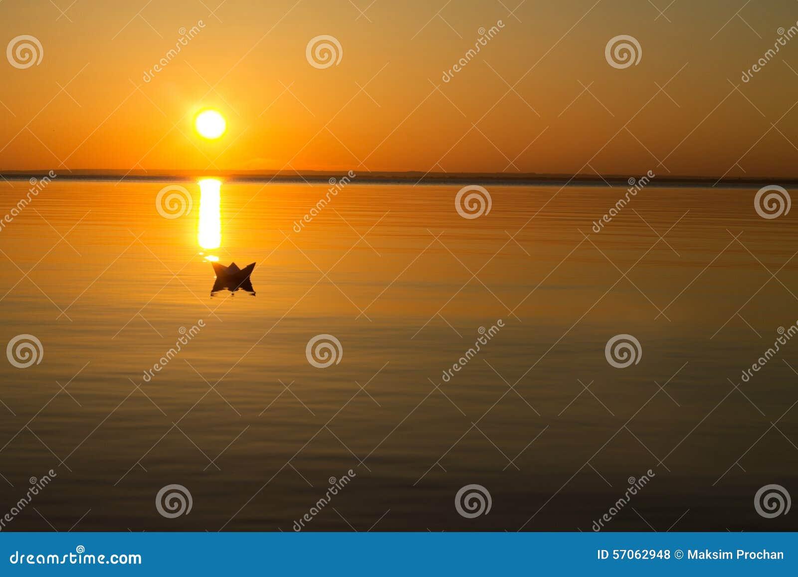 Document boot die in het water tijdens zonsondergang drijven