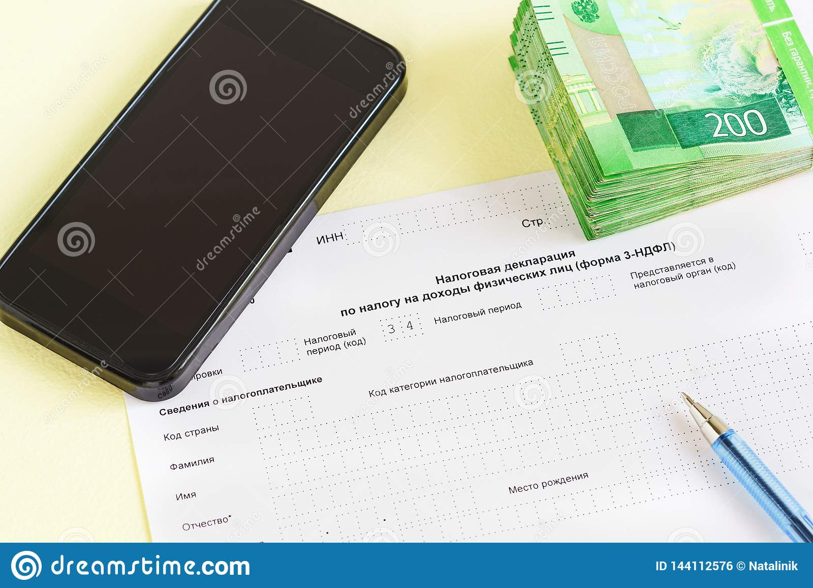 Document in Russische taal: Van de Belastingsverklaring op de belasting aan inkomens van fysiek personenclose-up, pen, smartphone