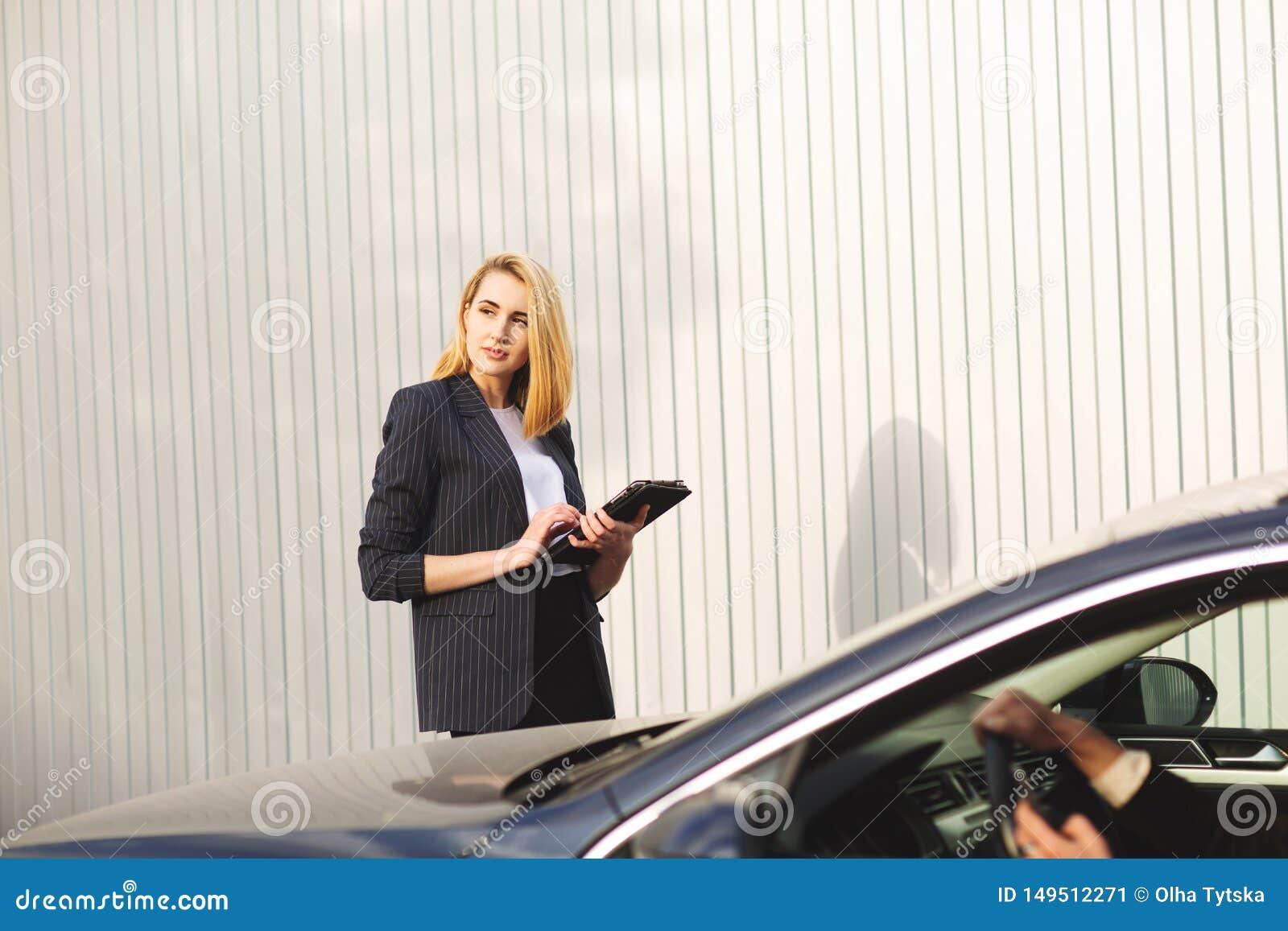 Documenten die door de vrouwenwerknemer, dichtbij de zwarte auto controleren