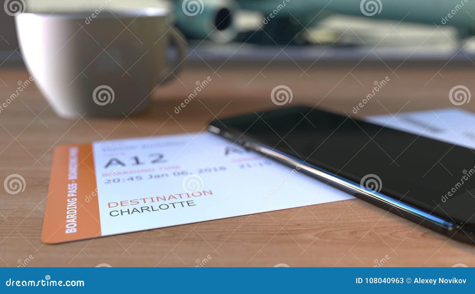 Documento de embarque a Charlotte y smartphone en la tabla en aeropuerto mientras que viaja a los Estados Unidos representación 3
