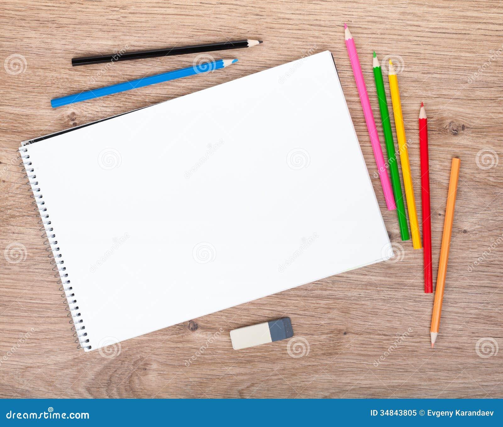 Documento en blanco y lápices coloridos sobre la tabla de madera