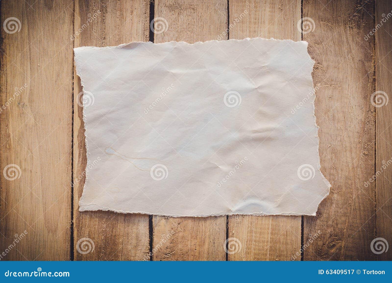 Documento rasgado viejo sobre el fondo de madera
