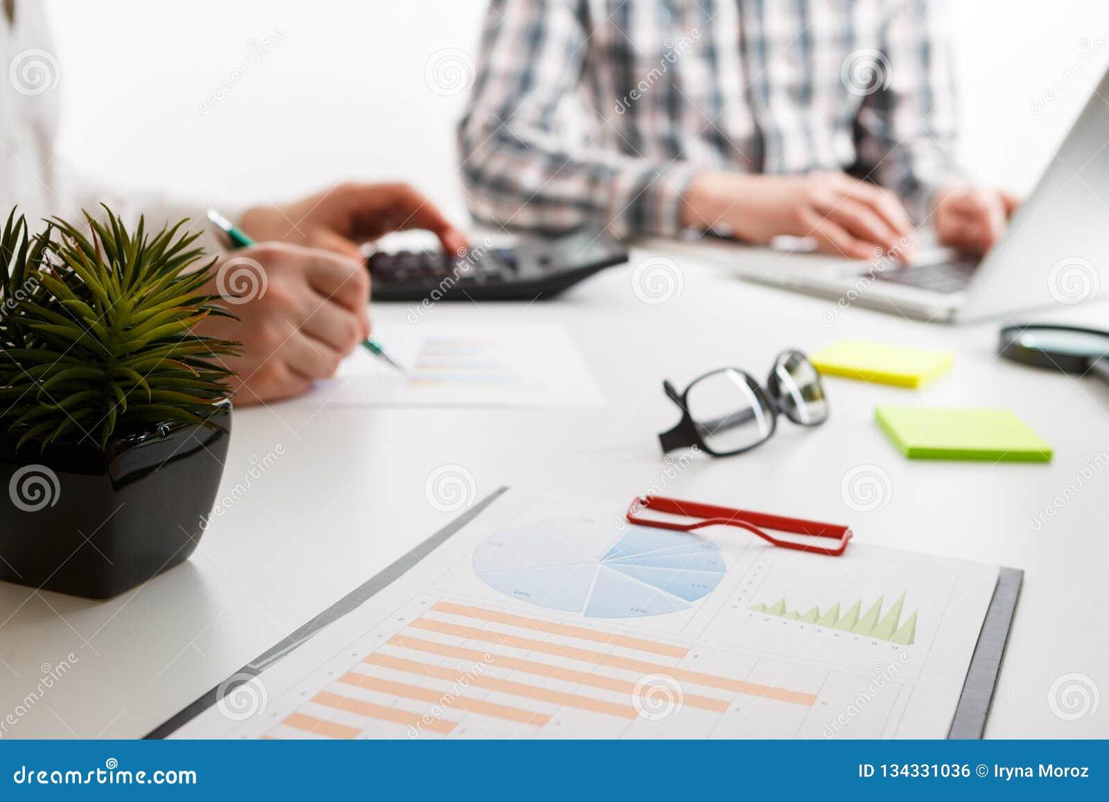 Documentos con la carta y el gráfico y pluma en el fondo del trabajo de dos empleados