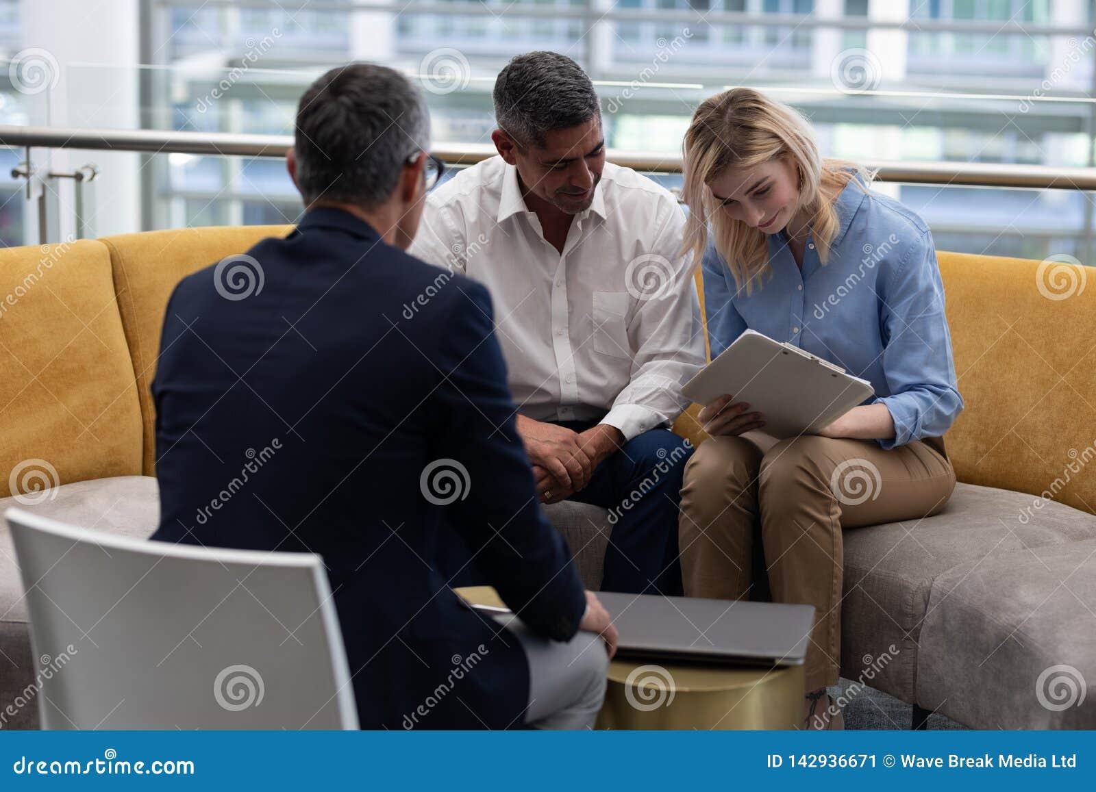 Documentos de assinatura da mulher de negócios loura dos Caucasians ao sentar-se no sofá