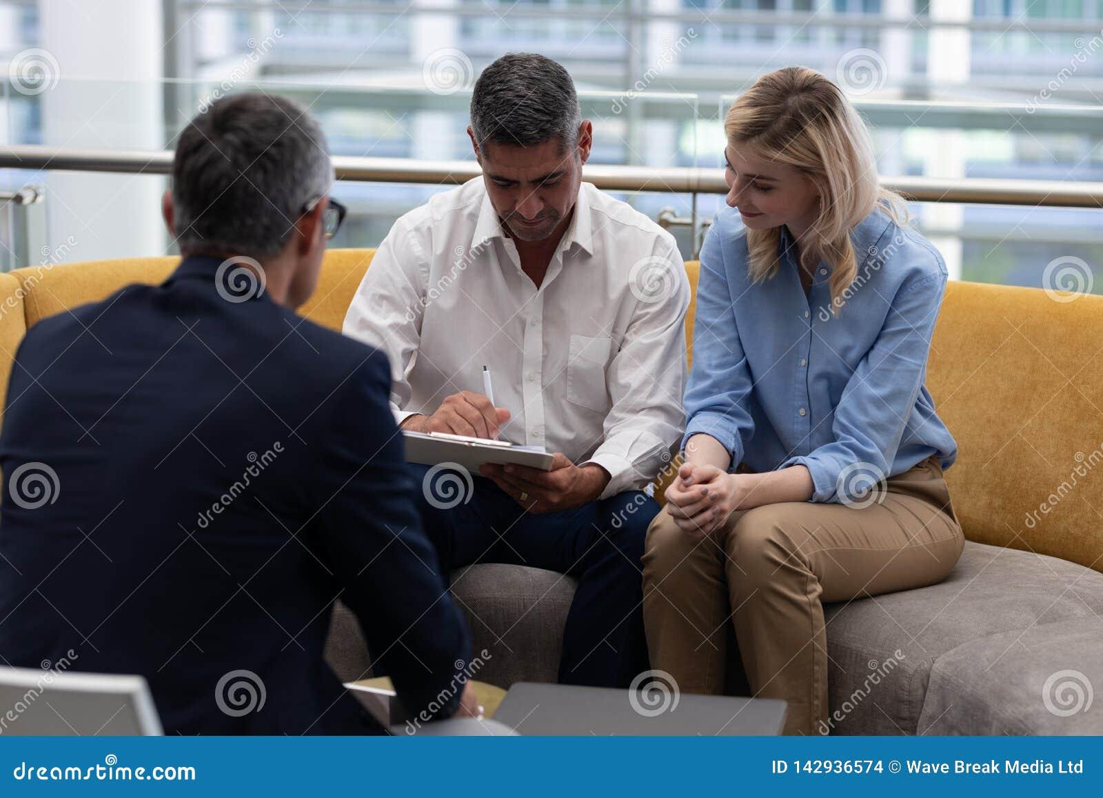 Documentos de assinatura do homem de negócios dos Caucasians ao sentar-se no sofá