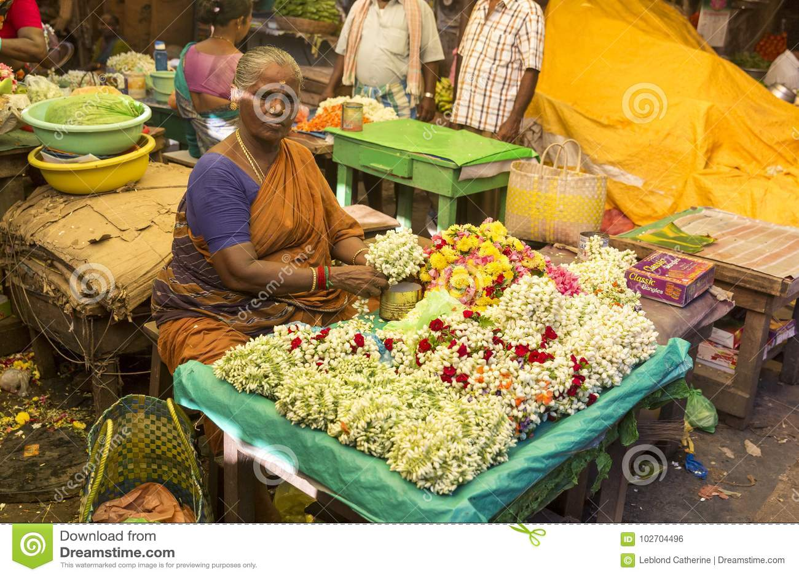 Documetary-Leitartikelbild Nicht identifizierter Mannfrauenverkauf, der Seile von Blumen Hauptmarkt am im Freien in Indien schaff