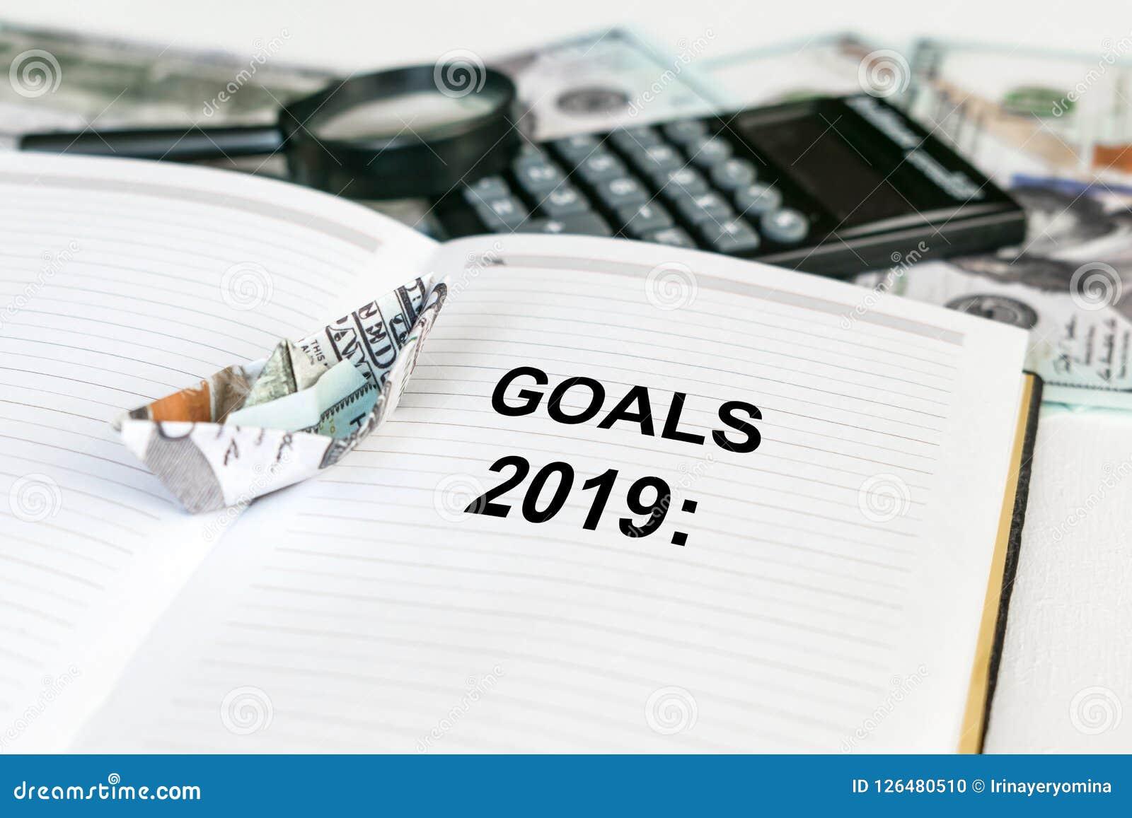 2019 doelstellingen de tekst in open notitieboekje met de origami van het dollarbankbiljet verscheept en calculator, geld en meer