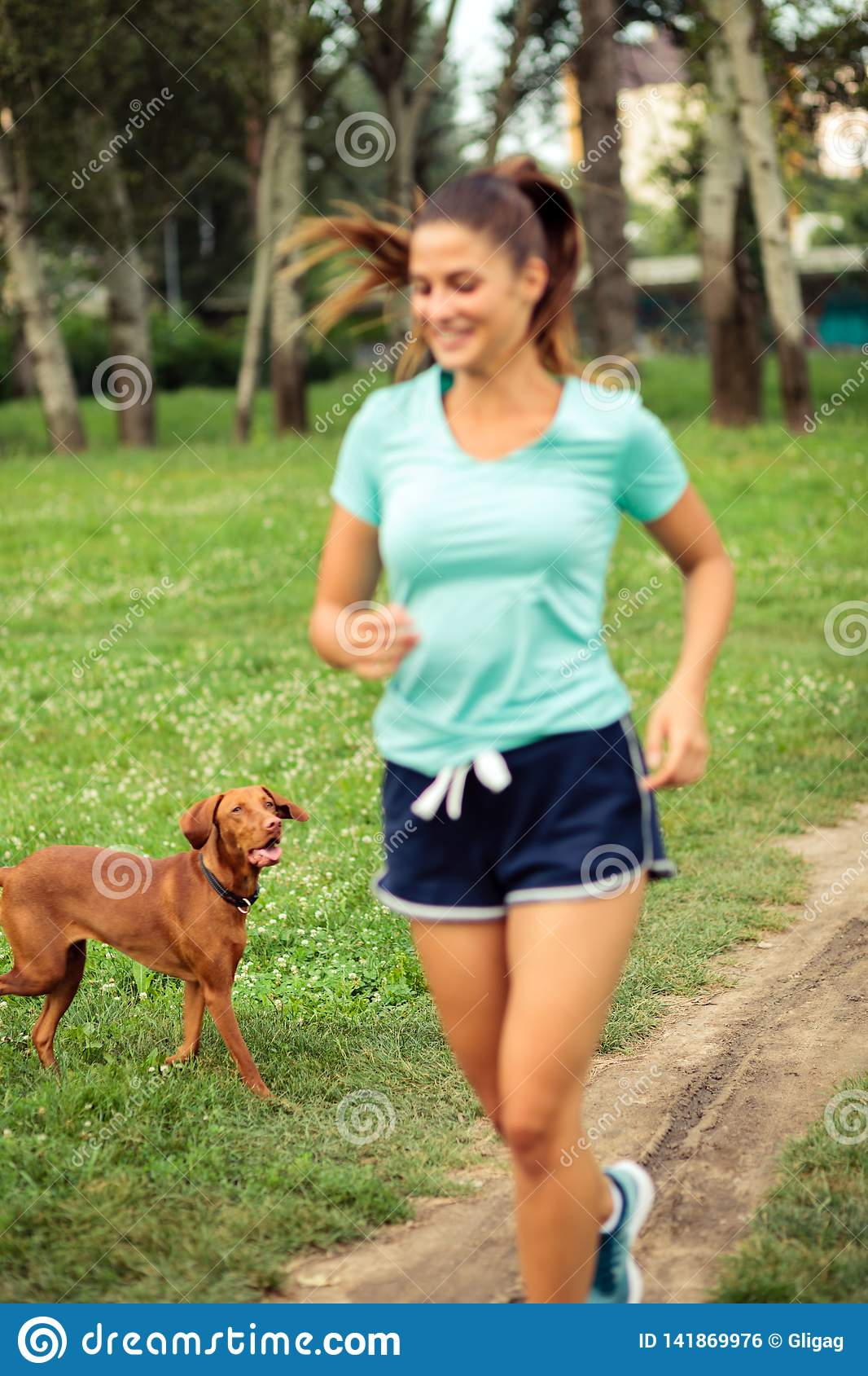 Dog following young woman while she is running in a park