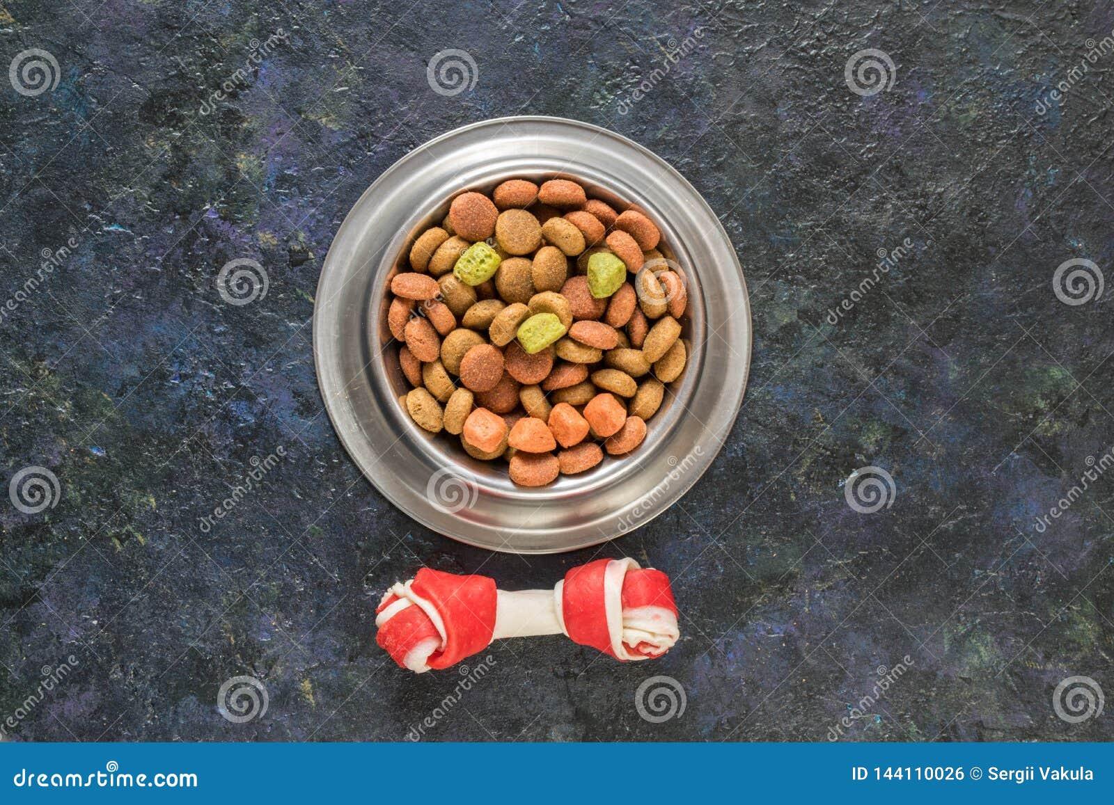 Dog food in metallic bowl on black dark blue background