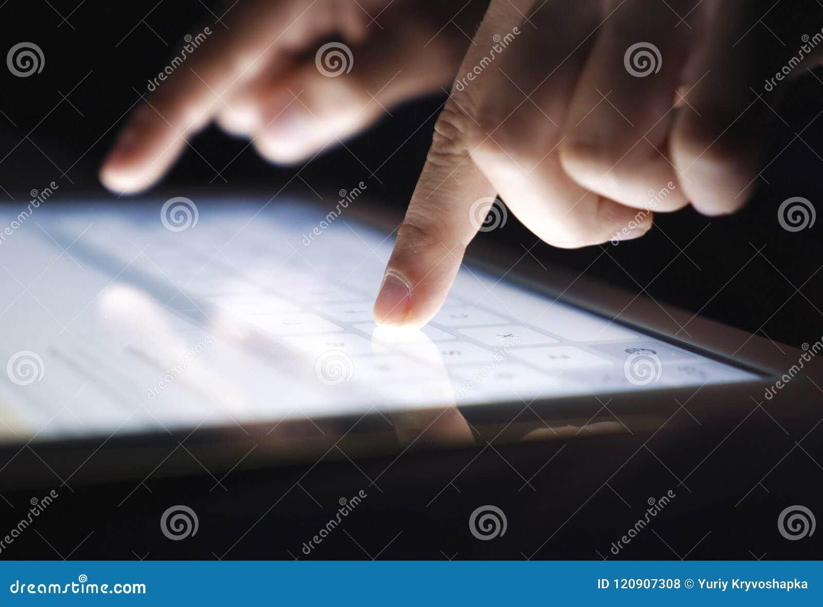 Doigts de plan rapproché dactylographiant textotant un message sur le comprimé