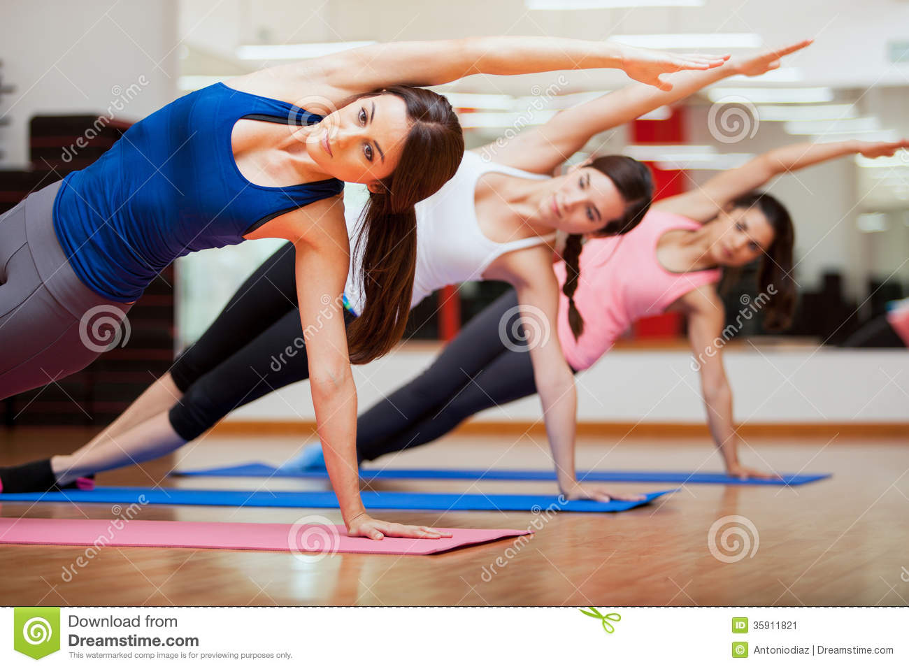 Doing A Side Plank For Yoga Class Beautiful Group Of Women Practicing The