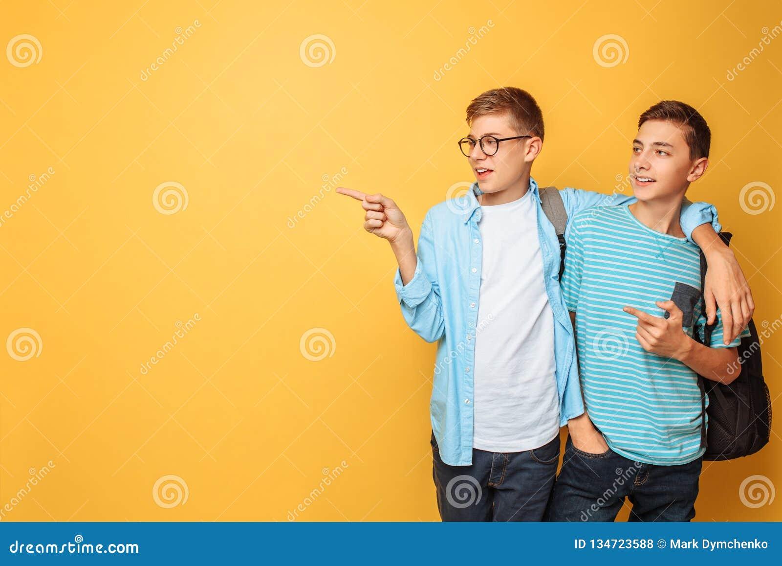 Dois adolescentes amigáveis, apontam o dedo no espaço vazio, em um fundo amarelo