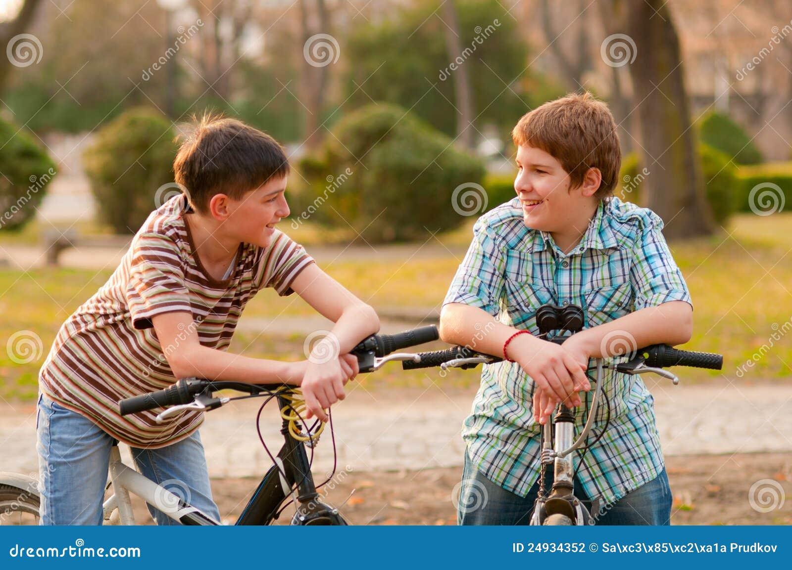 Dois adolescentes felizes nas bicicletas que têm o divertimento