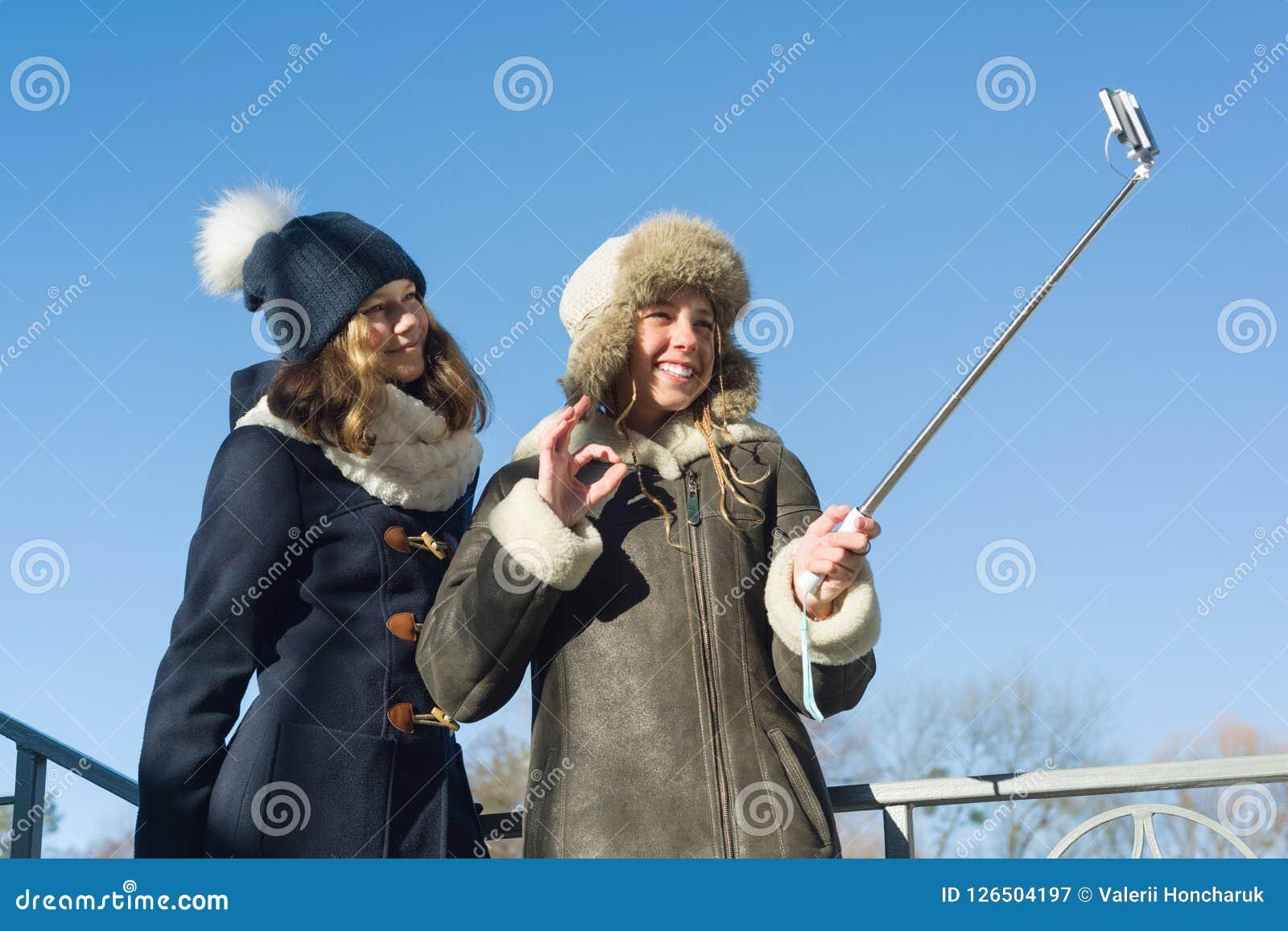 Dois adolescentes novos que têm o divertimento fora, amigas de sorriso felizes no inverno vestem a tomada do selfie, de povos pos