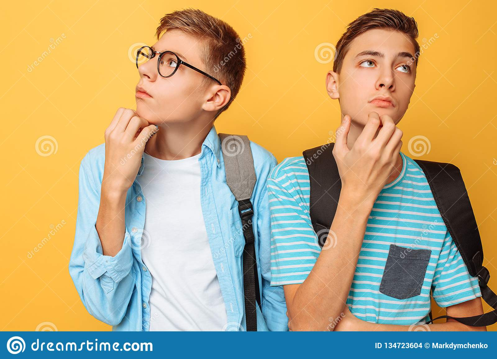 Dois adolescentes pensativos, indivíduos que estão tentando encontrar a solução direita ou fazer planos, em um fundo amarelo