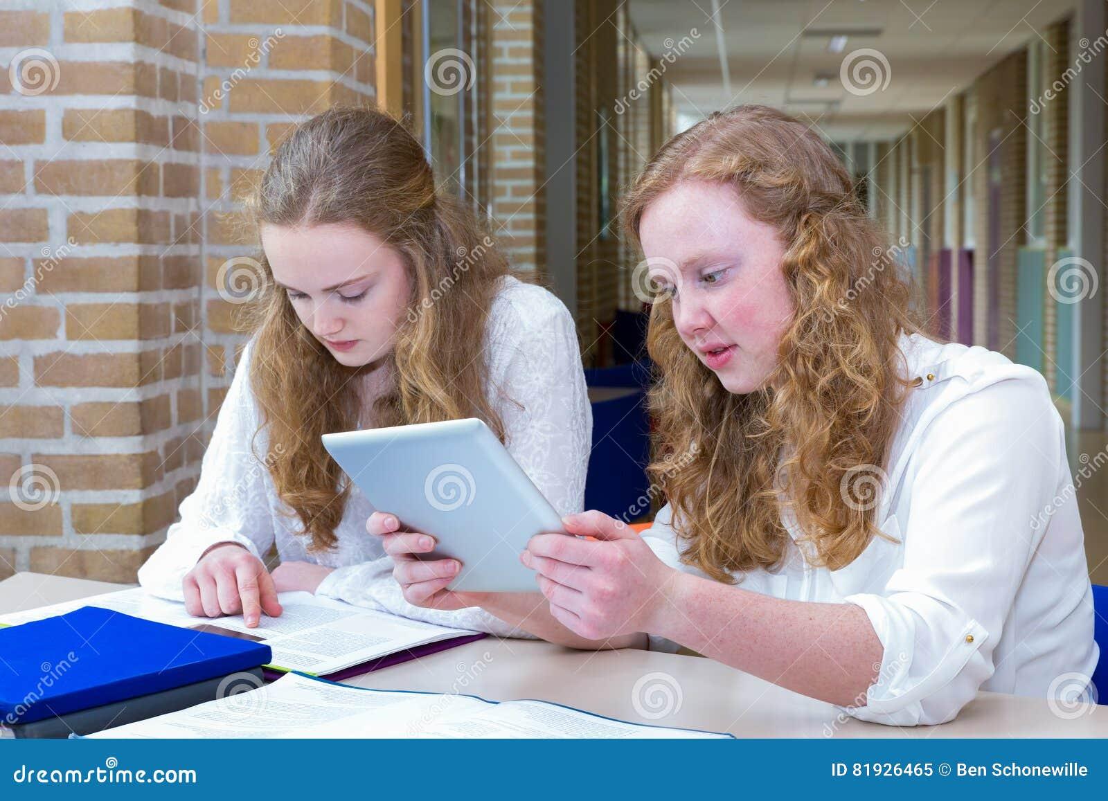 Dois adolescentes que estudam no corredor da escola