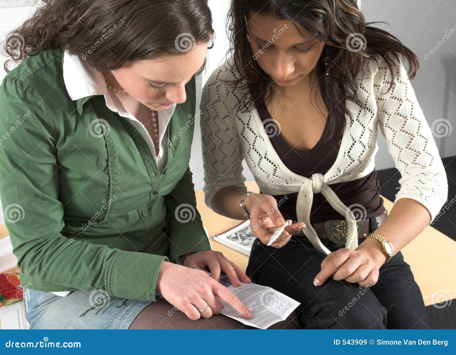 Dois adolescentes que verific o teste de gravidez