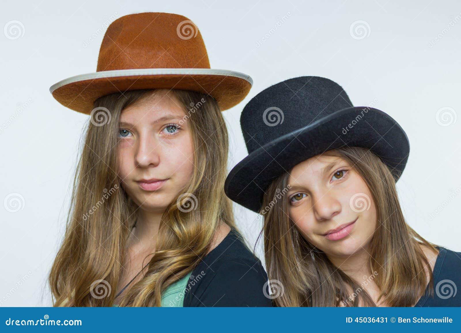 Dois adolescentes que vestem chapéus