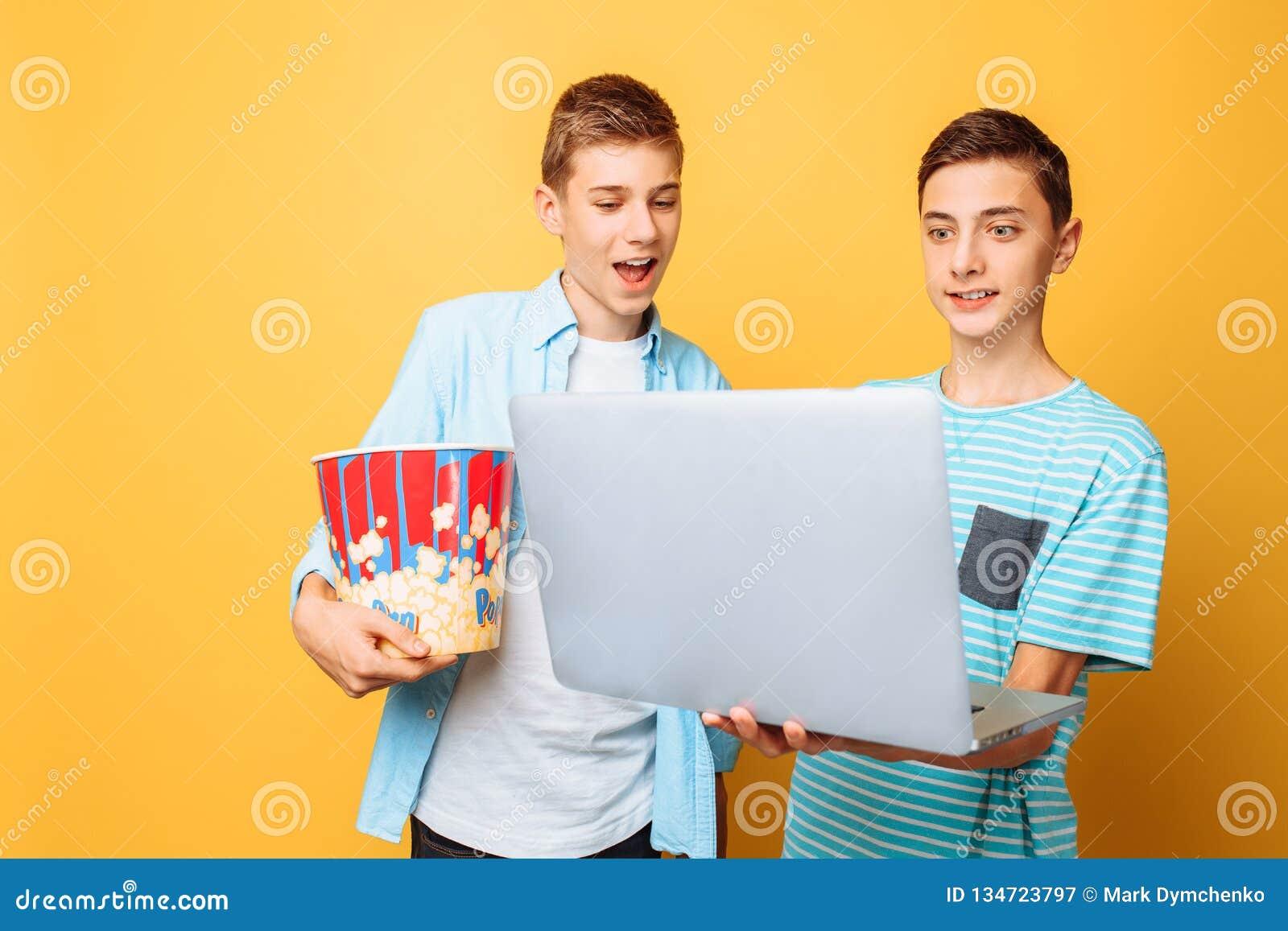Dois amigos adolescentes com uma cubeta da pipoca em suas mãos e em um portátil que prepara-se para olhar filmes em um fundo amar