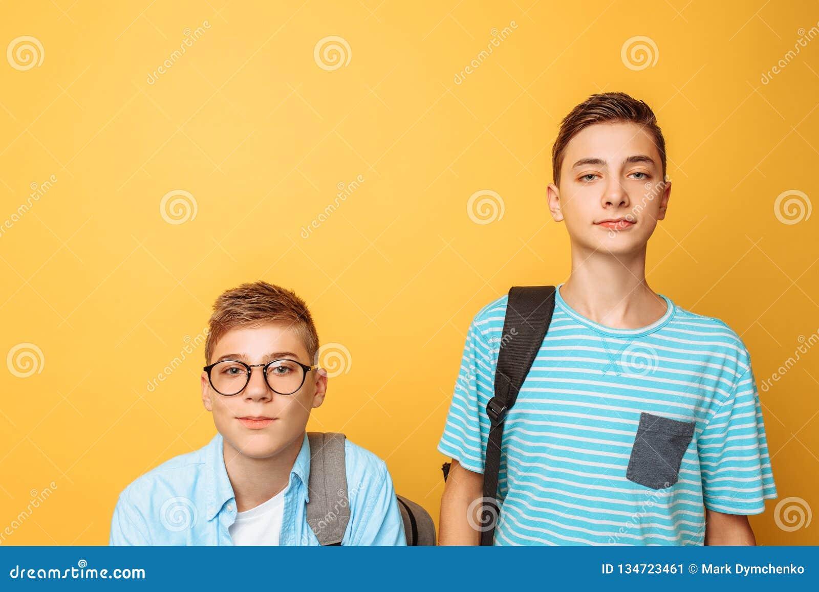 Dois amigos adolescentes, um indivíduo humilham o outro, popular humilham o impopular, em um fundo amarelo