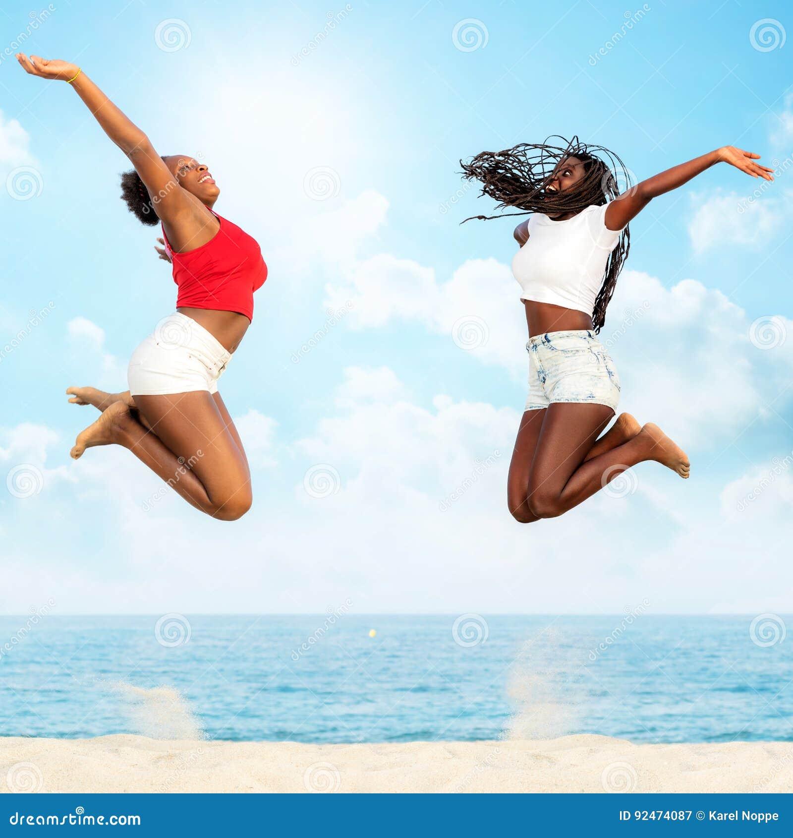 Dois amigos africanos que saltam junto na praia