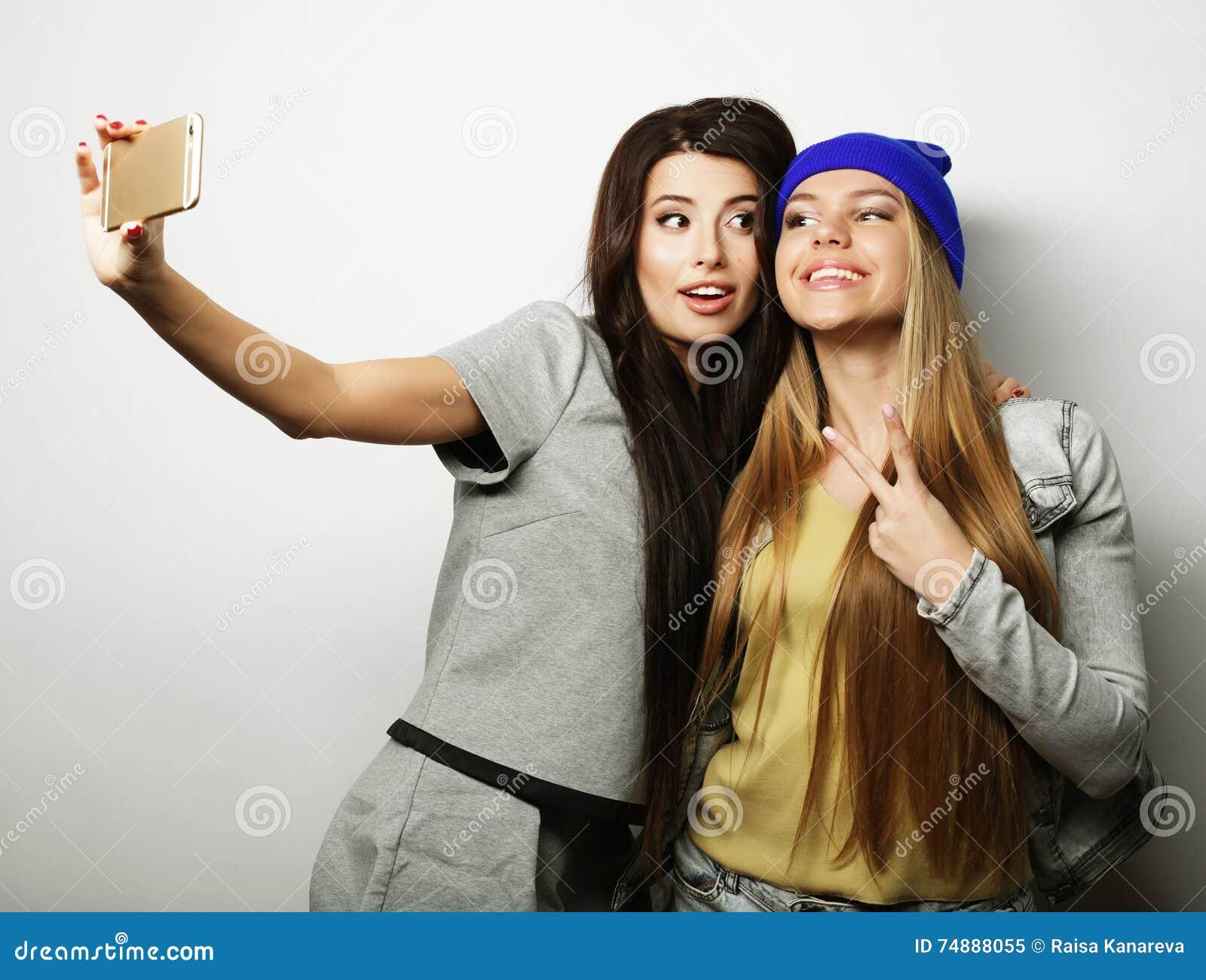 Dois amigos de adolescentes no equipamento do moderno fazem o selfie