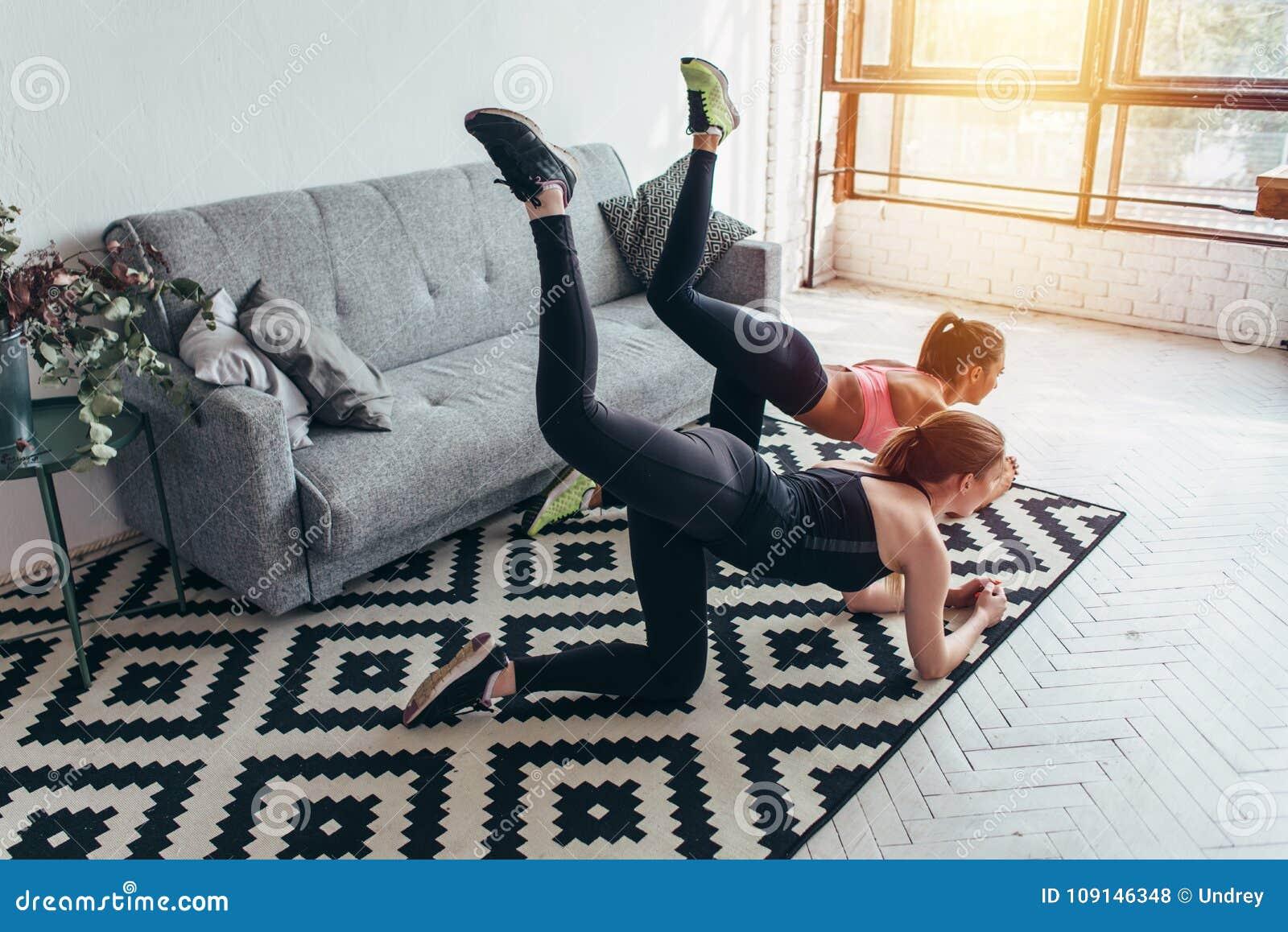 Dois amigos fêmeas desportivos que fazem a extremidade que tonifica o asno de execução do exercício retrocedem em casa
