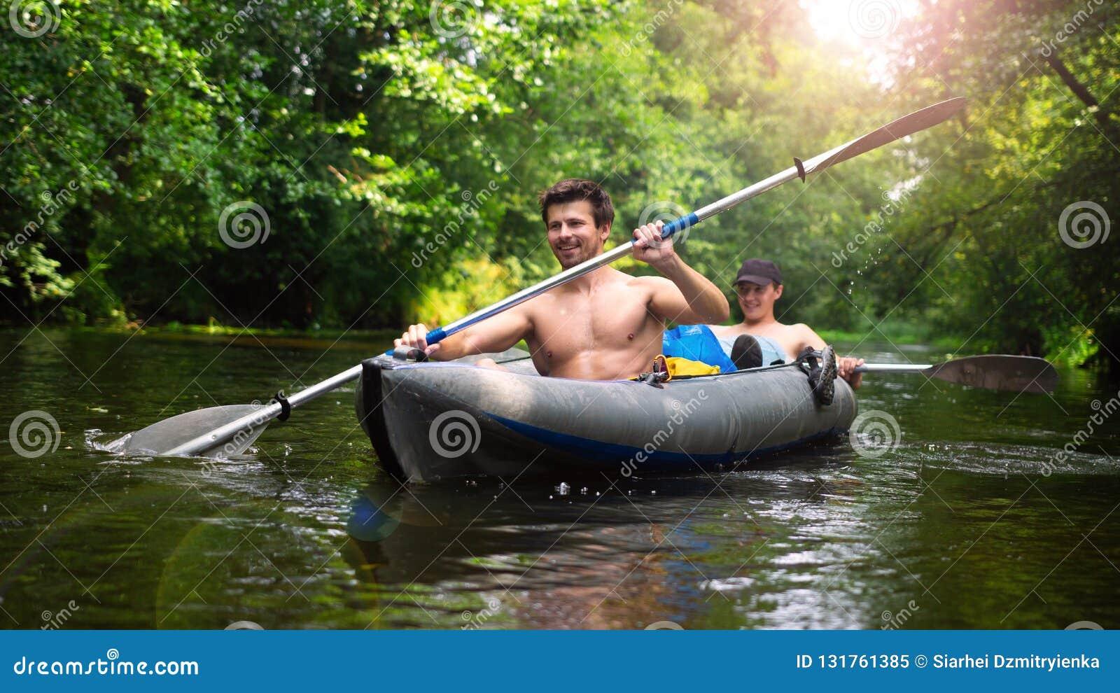 Dois amigos nadam no caiaque no rio selvagem da selva