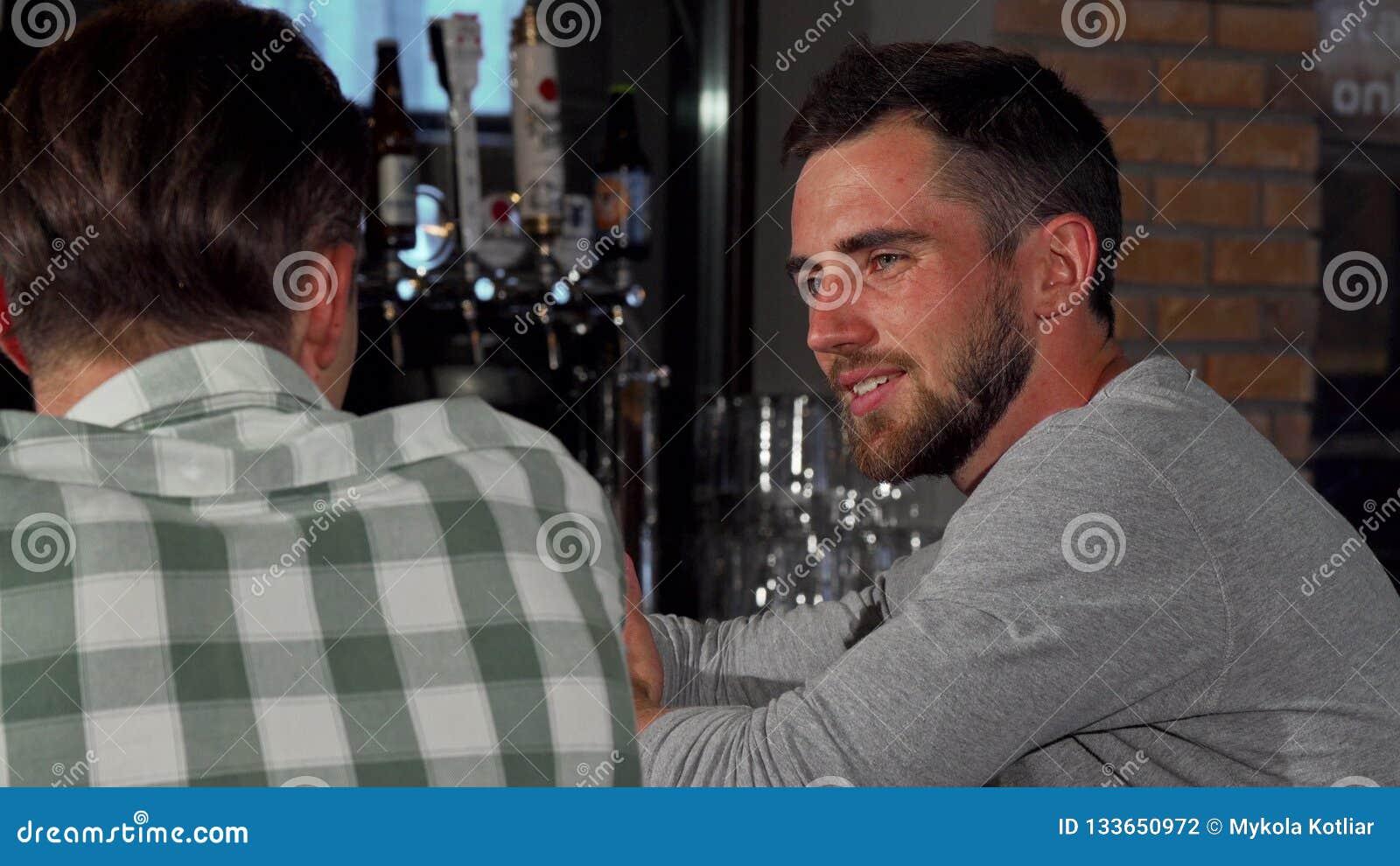 Dois amigos que conversam sobre a cerveja no bar local