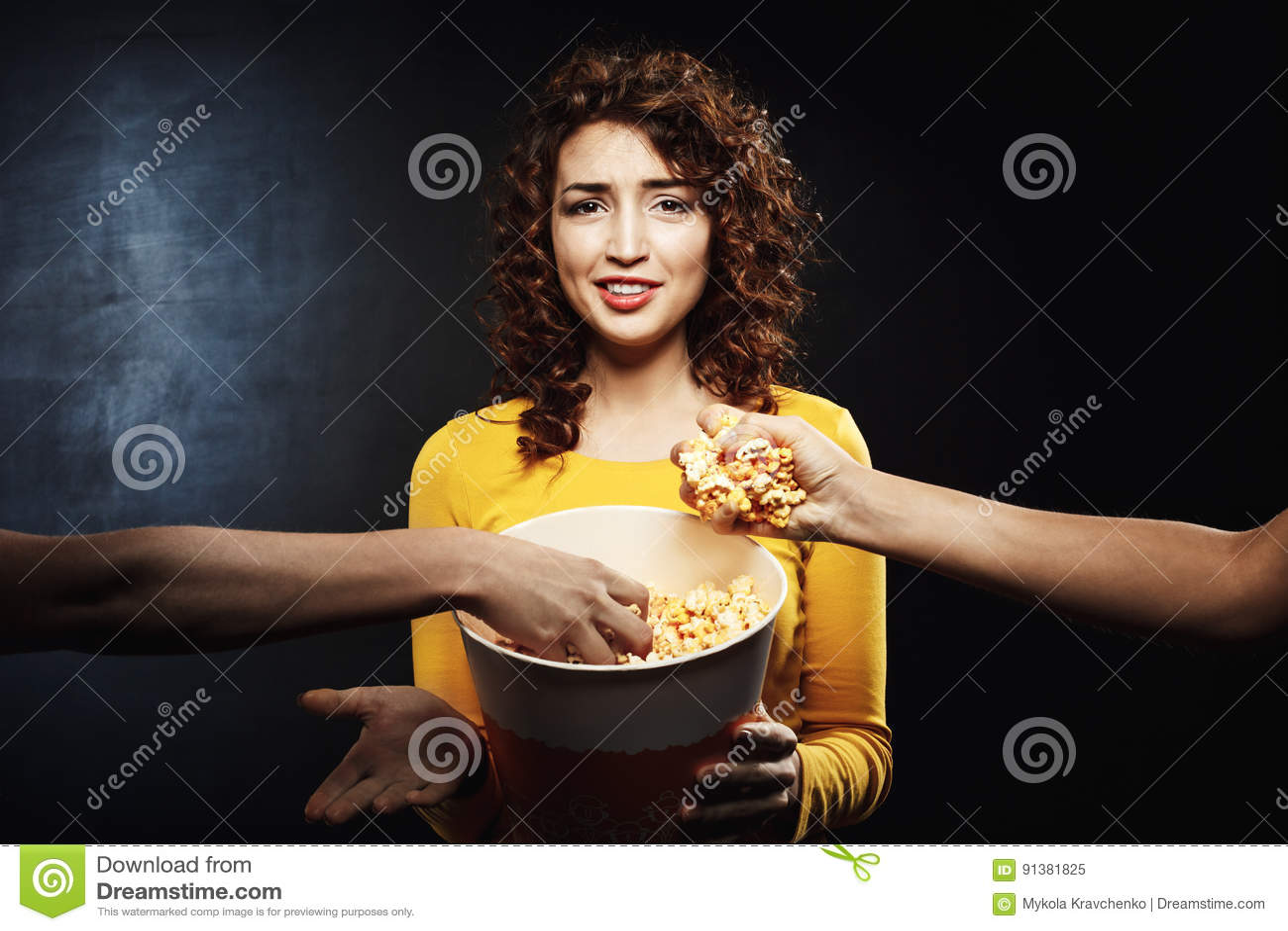 Dois amigos que tomam a pipoca da cubeta do ` s da menina Emoções faciais negativas